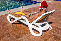 A man in a Santa Claus cap on a lounger by the pool on a tropica Royalty Free Stock Images