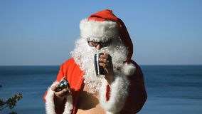 A man in a Santa Claus costume with cocktail shaker is dancing on the seashore. Travel and vacation. A man in a Santa Claus costume with cocktail shaker is stock video