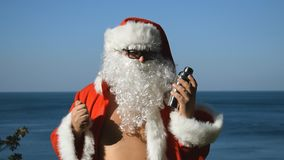 A man in a Santa Claus costume with cocktail shaker is dancing on the seashore. Travel and vacation. A man in a Santa Claus costume with cocktail shaker is stock footage