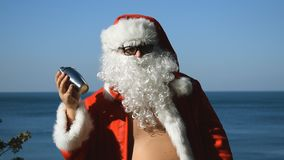 A man in a Santa Claus costume with cocktail shaker is dancing on the seashore. Travel and vacation. A man in a Santa Claus costume with cocktail shaker is stock video footage