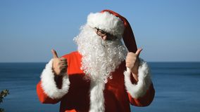 A man in a Santa Claus costume is dancing on the seashore. Travel and vacation. A man in a Santa Claus costume is dancing on the seashore stock video