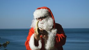 A man in a Santa Claus costume eating banana on the seashore. Travel and vacation stock video footage