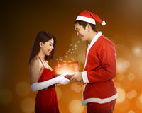 Man in santa claus costume give present box to woman Stock Photography