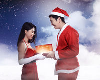 Man in santa claus costume give present box to woman Royalty Free Stock Images