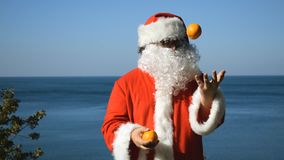 A man in a Santa Claus costume juggles tangerines on the seashore. Travel and vacation. A man in a Santa Claus costume juggles tangerines on the seashore stock video footage