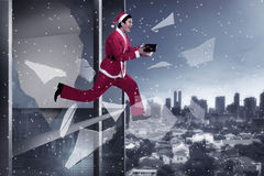 Man in santa claus costume jumping from building Royalty Free Stock Images