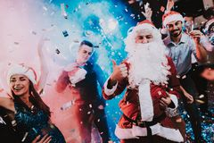 Man in Santa Claus Costume on New Year Party. Happy New Year. People Have Fun. Indoor Party. Celebrating of New Year. Young Women in Dresses. Young Men in stock images