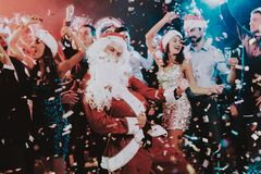 Man in Santa Claus Costume on New Year Party. Happy New Year. People Have Fun. Indoor Party. Celebrating of New Year. Young Women in Dresses. Young Men in stock photos