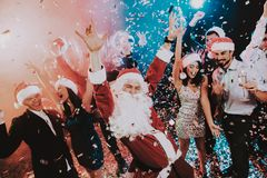 Man in Santa Claus Costume on New Year Party. Happy New Year. People Have Fun. Indoor Party. Celebrating of New Year. Young Women in Dresses. Young Men in royalty free stock photos