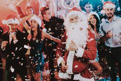 Man in Santa Claus Costume on New Year Party. Happy New Year. People Have Fun. Indoor Party. Celebrating of New Year. Young Women in Dresses. Young Men in royalty free stock photo