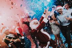 Man in Santa Claus Costume on New Year Party. Happy New Year. People Have Fun. Indoor Party. Celebrating of New Year. Young Women in Dresses. Young Men in stock photo