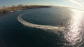 A man in Santa Claus costume rides on jetsurf beside beautiful ocean coast Aerial view stock footage