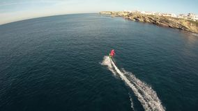 A man in Santa Claus costume rides on jetsurf beside beautiful ocean coast Aerial view stock video footage