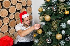 Man in santa claus hat decorate Christmas tree. With balls, snowflakes, garlands on wood logs background. xmas, new year, eve, holidays celebration. Festive stock photos