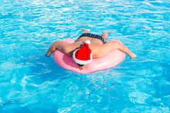 Man in santa claus hat walking in the swimming pool on sunny day ,feeling relax.  Stock Photography