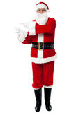 Man in Santa costume indicating at copy space area Royalty Free Stock Photos