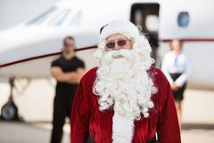 Man In Santa Costume Standing Against Private Jet stock photo