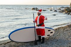 Santa on SUP board. Man in Santa costume with SUP board on winter sea Royalty Free Stock Photography