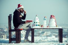 Man santa drinking coffee on winter day. Hipster reading book on chair. Snowmen and snow xmas tree on wooden table. Christmas and new year holidays celebration royalty free stock images