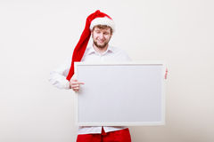 Man in santa hat with blank banner. Copy space. Stock Image