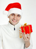 Man in a Santa hat with Christmas gift Stock Photos