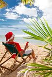 Man in Santa hat with cocktail on a beach Royalty Free Stock Images