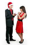 Man in Santa hat gives a woman a ring Royalty Free Stock Photo