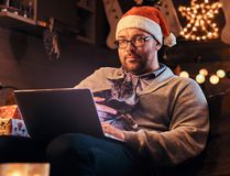 Man in Santa hat and glasses dressed in warm sweater holds cat and using laptop celebrating Christmas at home. stock photos