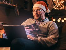 Man in Santa hat and glasses dressed in warm sweater holds cat and using laptop celebrating Christmas at home. royalty free stock photography