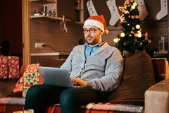 Man in Santa hat and glasses dressed in warm sweater working on laptop at Christmas. royalty free stock photos