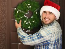 Man in Santa hat hanging Christmas wreath. On door Stock Images