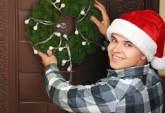 Man in Santa hat hanging Christmas wreath. On door Stock Photography