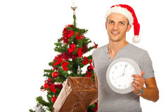 Man with Santa hat holding clock Stock Photo