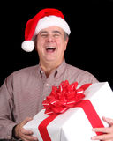 Man with Santa hat holding a present Stock Images
