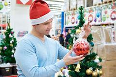 Man in Santa hat holding red ball Christmas tree Royalty Free Stock Photography