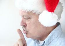 Man in Santa hat with hush gesture Royalty Free Stock Image