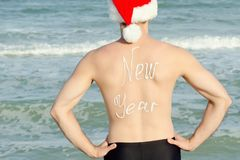 Man in Santa hat with the inscription New year on the back stand Royalty Free Stock Photography