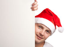 Man with santa hat peeking out of blank poster Royalty Free Stock Photos