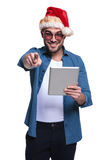 Man with santa hat is pointing  while reading on tablet Stock Photo