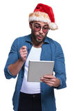 Man in santa hat is reading something surprising on pad Royalty Free Stock Photos
