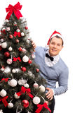 Man with Santa hat standing behind a Christmas tree Royalty Free Stock Image