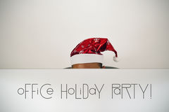 Man with santa hat and text office holiday party. Man with a santa hat, behind the screen of his computer where you can read office holiday party, sitting at his royalty free stock photography