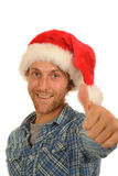 Man in Santa hat with thumb up. Happy young man in Santa hat with thumb up; isolated on white background Royalty Free Stock Images