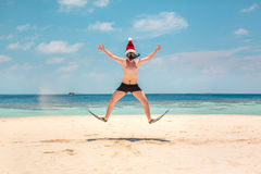 Man in santa hat on the tropical beach Stock Photos