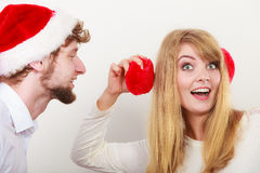 Man in santa hat whispering to woman ear. Man boyfriend in santa claus hat whispering to women girlfriend ear. Gossip couple on gray. Christmas xmas season Royalty Free Stock Image