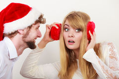 Man in santa hat whispering to woman ear. Man boyfriend in santa claus hat whispering to women girlfriend ear. Gossip couple on gray. Christmas xmas season Royalty Free Stock Photography