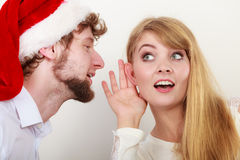 Man in santa hat whispering to woman ear. Man boyfriend in santa claus hat whispering to women girlfriend ear. Gossip couple on gray. Christmas xmas season Stock Photography