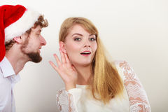 Man in santa hat whispering to woman ear. Stock Photo