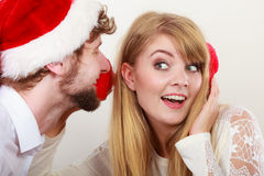 Man in santa hat whispering to woman ear. Man boyfriend in santa claus hat whispering to women girlfriend ear. Gossip couple on gray. Christmas xmas season Royalty Free Stock Images