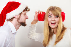 Man in santa hat whispering to woman ear. Man boyfriend in santa claus hat whispering to women girlfriend ear. Gossip couple on gray. Christmas xmas season Stock Photo